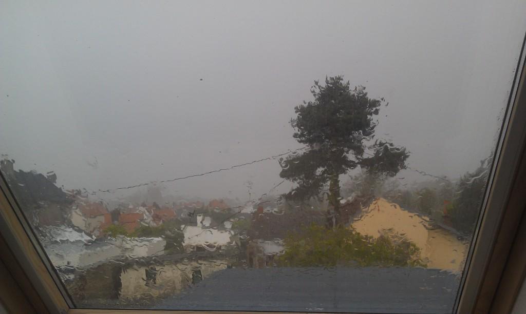 La vue sur le village, depuis la fenêtre de ma chambre, à travers un rideau de pluie.